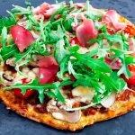Lowcarb Pizza aus Blumenkohlsraspeln, belegt mit Champignons, Rucola und Serranoschinken